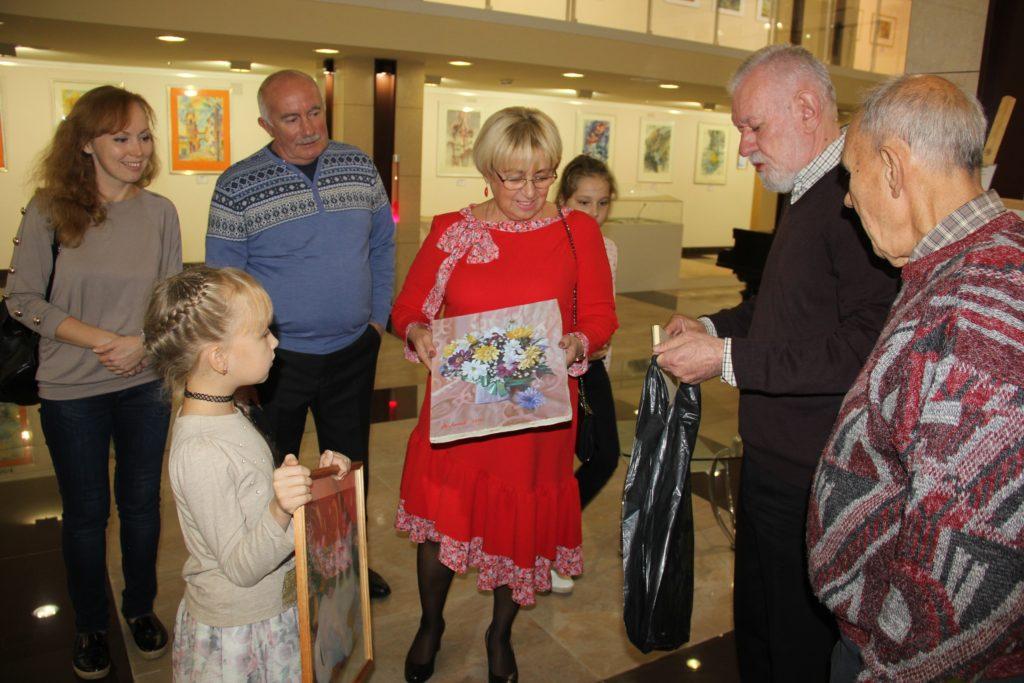 Výměna obrázků Ariny s malířem A.Lysovem (druhý zprava) Uprostřed Ljubov Šumilkina